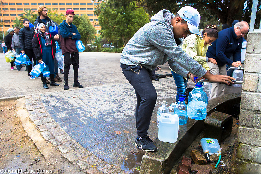 Capetonians fill up their water containers at the Newlands spring in a suburb of Cape Town. The spring, whose water is supplied by nearby Table Mountain, has flowed without interruption since record keeping started in South Africa, but has only recently becoming a critical collection point. Because of rising water costs and tight restrictions on municipal water usage, local residents come to the spring to fill up on the clean mountain water they use primarily for drinking and cooking.