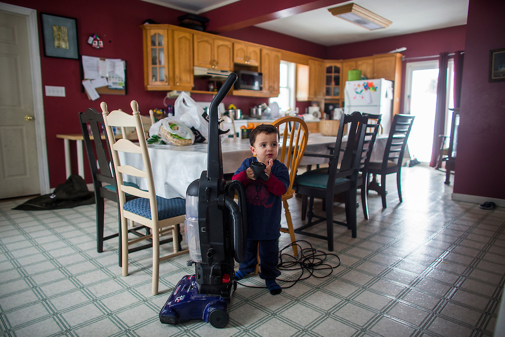 Syrian refugee Fadl Al Jasem plays with the vacuum inside their temporary home in Picton, Ontario, Canada, Wednesday January 20, 2016.   (Mark Blinch for the BBC)
