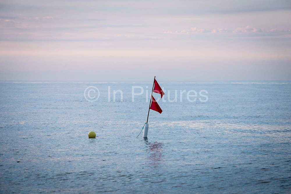 Marker buoy floating in the sea with flags attached to show a location of a Lobster or crab pot Hythe Bay, the English Channel, United Kingdom.