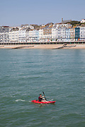 A man kayaking along Hastings seafront on the 20th April 2019 in Hastings in the United Kingdom. Hastings is a town on England's southeast coast, its known for the 1066 Battle of Hastings.