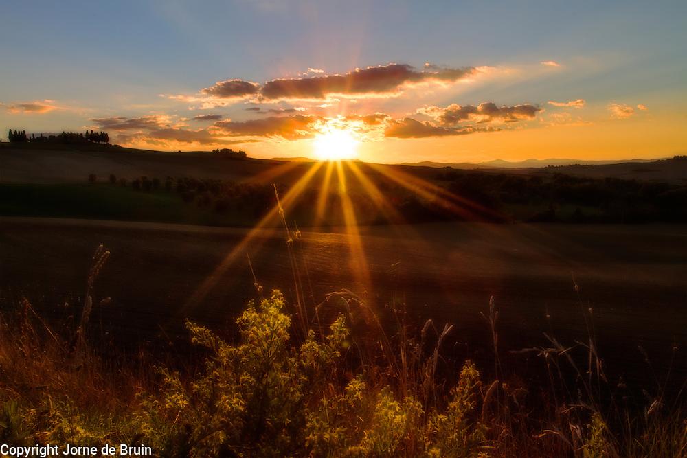 Dreamlike sunset over Tuscan farmland in autumn.