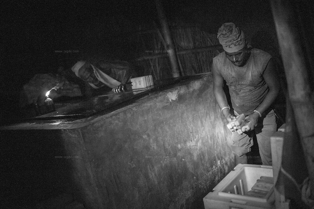 3:30am. To the light of a single candle, the ice packs are taken out of the ice factory and placed into the cold boxes. They are then carried on the head and on bicycle carts, bare footed through thick mud, to the river were they are loaded onto boats that take the vaccine to a sub depots to be distributed to vaccinator teams and reach more than two hudred villages on the flood plains of the Kosi river. Kusheshwar Asthan east, Bihar.