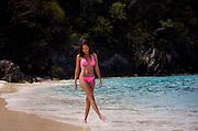 A woman in a bikini kicks through the water as she walks along the shore of a carribean ocean.