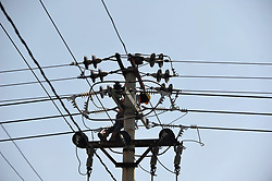 October 3, 2018 - Palu, Indonesia - PALU, CENTRAL SULAWESI, OCTOBER - 03: officers check electrical equipment such as cables and others on a pole in the city of Palu, Central Sulawesi, on October 03 2018. It has been 5 days since the Palu city has passed the night without lighting due to an earthquake which damaged electrical components and it takes time to bring in the damaged components so that the residents have difficulty in doing activities in the household. Dasril Roszandi  (Credit Image: © Dasril Roszandi/NurPhoto/ZUMA Press)