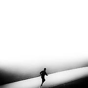 A jogger enjoys a run through a park on a foggy day in Vancouver. Photo: © Rod Mountain