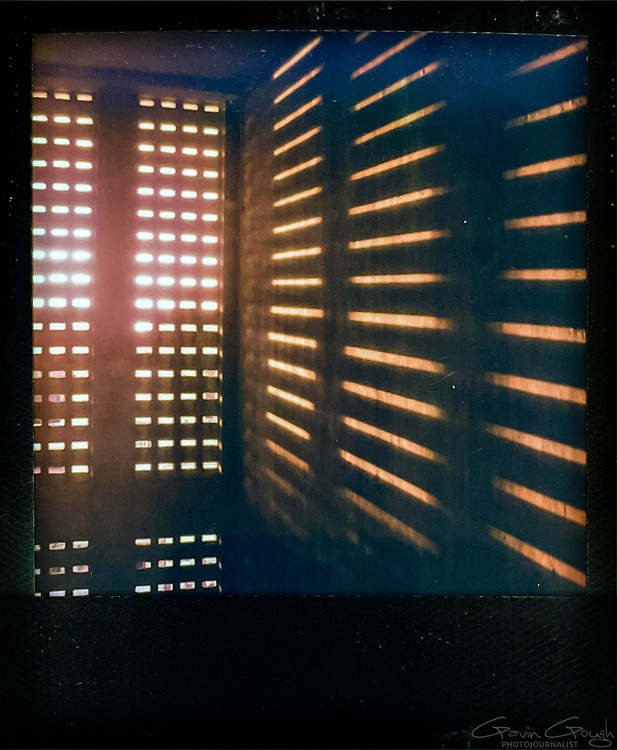 Sunlight shining through gaps in shutters in a cell block stairway, Tuol Sleng S-21 Genocide Museum, Cambodia