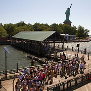 The Statue of Liberty stands tall as visitors board the boat that will take them on to Ellis Island.