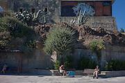Remote-lookig men seted on the seafront at Estoril near Lisbon, Portugal.