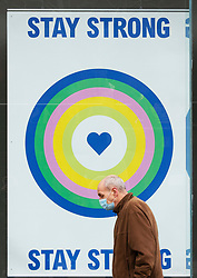 © Licensed to London News Pictures 17/03/2021. Bexleyheath, UK. A man walking past a stay strong poster. People out and about shopping in Bexleyheath, South East London today are wearing masks to protect themselves during a third national coronavirus lockdown. Everyone over the age of fifty is now eligible for a Covid vaccine in the UK. Photo credit:Grant Falvey/LNP