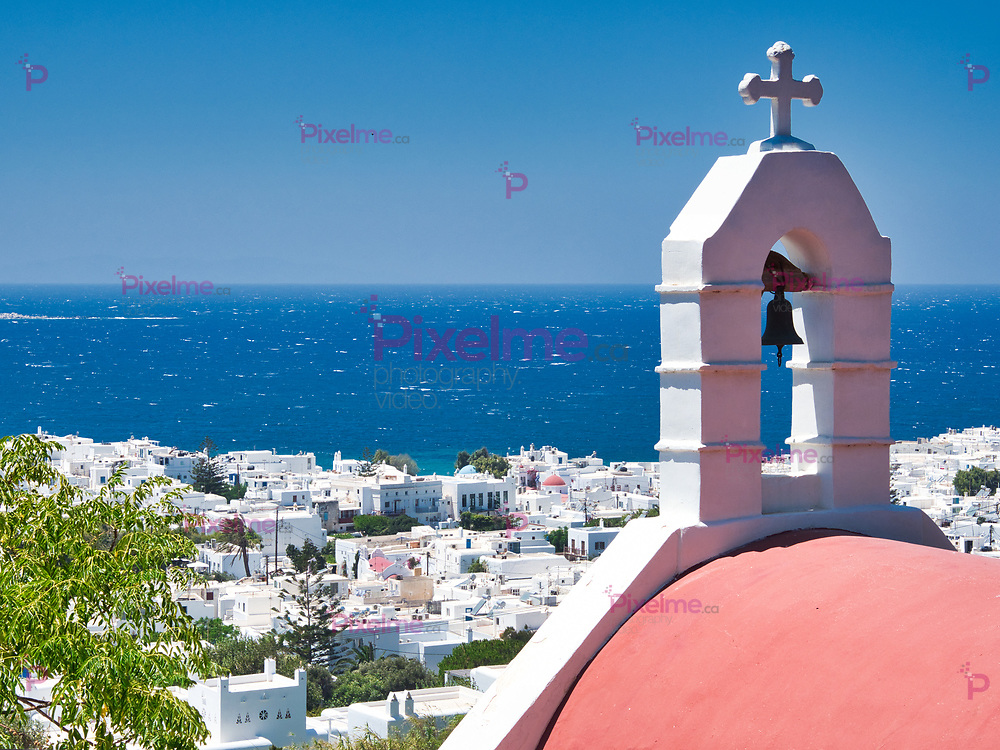 Roof of church with cross and bell located in coastal town against blue sea and cloudless sky on Mykonos Island on sunny day in Greece