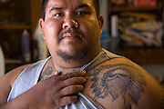 Assistant carpenter and tattooist Louie Soto showing off his tattoos at his home in Sacaton, Arizona. (Louie Soto is featured in the book What I Eat: Around the World in 80 Diets.) He is 30 years of age; 5 feet, 9 inches tall; and 320 pounds. Soto built a new home, financed by casino profits and built by the Gila River Indian Community. MODEL RELEASED.