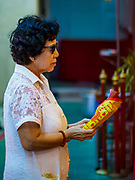 """22 AUGUST 2017 - BANGKOK, THAILAND: A woman prays during a ceremony on the first day of Hungry Ghost Month at the Poh Teck Tung Shrine in Bangkok's Chinatown. The seventh lunar month (August - September) is when many Chinese believe Hell's gate will open to allow spirits to roam freely in the human world. Many households and temples hold prayer ceremonies throughout the month-long Hungry Ghost Festival (Phor Thor) to appease the spirits. During the festival, believers will also worship the Tai Su Yeah (King of Hades) in the form of paper effigies which will be """"sent back"""" to hell after the effigies are burnt.      PHOTO BY JACK KURTZ"""