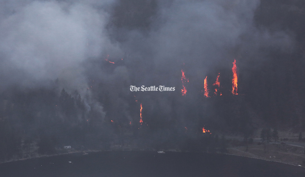 Trees erupt on the south side of Lake Chelan as the First Creek Wildfire descends to the water, Friday August 21, 2015.<br /> <br /> Alan Berner / The Seattle Times