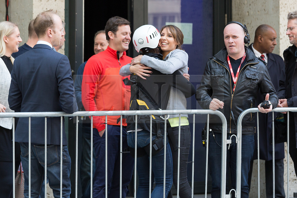 """© Licensed to London News Pictures. 10/06/2015. London, UK. Emma Willis hugs Alex Jones before taking part in a """"leap of faith"""" stunt at the new BBC Broadcasting House. Photo credit : Vickie Flores/LNP"""