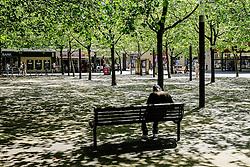 A man sits in dappled sunlight in Basildon Town Centre. Essex