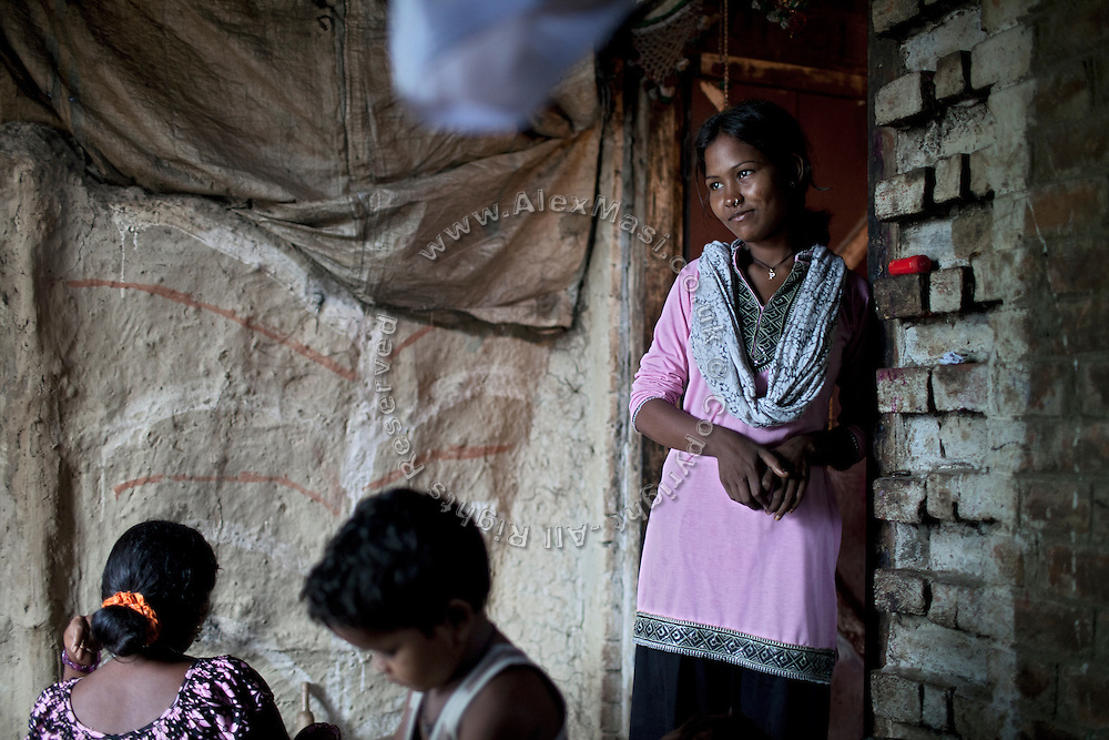 (name changed) Neelam Bharadwaj, 16, (right) is standing inside her family's home in Rajbhar village, located around 20 kilometres away from Varanasi, in Uttar Pradesh, India, while her older sister Sanju, 29, (left) is cooking. Neelam was raped when she was 13 years old. After walking to a local shop on the main road neighbouring her village, she was forcibly picked up by two men. While one of them was raping her in the bushes, the other watched out. After some time, she managed to free herself and run away, hiding under a bridge in cold dirty water for several hours. When she returned home in the morning, the family was too afraid to go to the police, but activist Mangla Parsad, 34, from PVCHR, convinced the family to take the right action. The police initially insulted and threatened the family for bringing the facts up, but filed the official case (FIR) nevertheless. The rape was not mentioned in the file due to an inaccurate and superficial medical record that did not, in fact, mention it. Because of social shame facing by victims of rape in India, the family agreed to wed Neelam to an older man, with help of an agent. After the marriage, her husband raped her again for a whole month before she decided to return home with her family. Neelam's father works in the metal industry in Mumbai and manages to send around 2-3000 INR every month. He only visits the family once in a year. Neelam goes to school and she is studying in 11th Class Standard. She is interested in doing BA in Arts after completing her high school 12th final year.