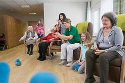 Girls playing bowling with nurse and senior women in rest home