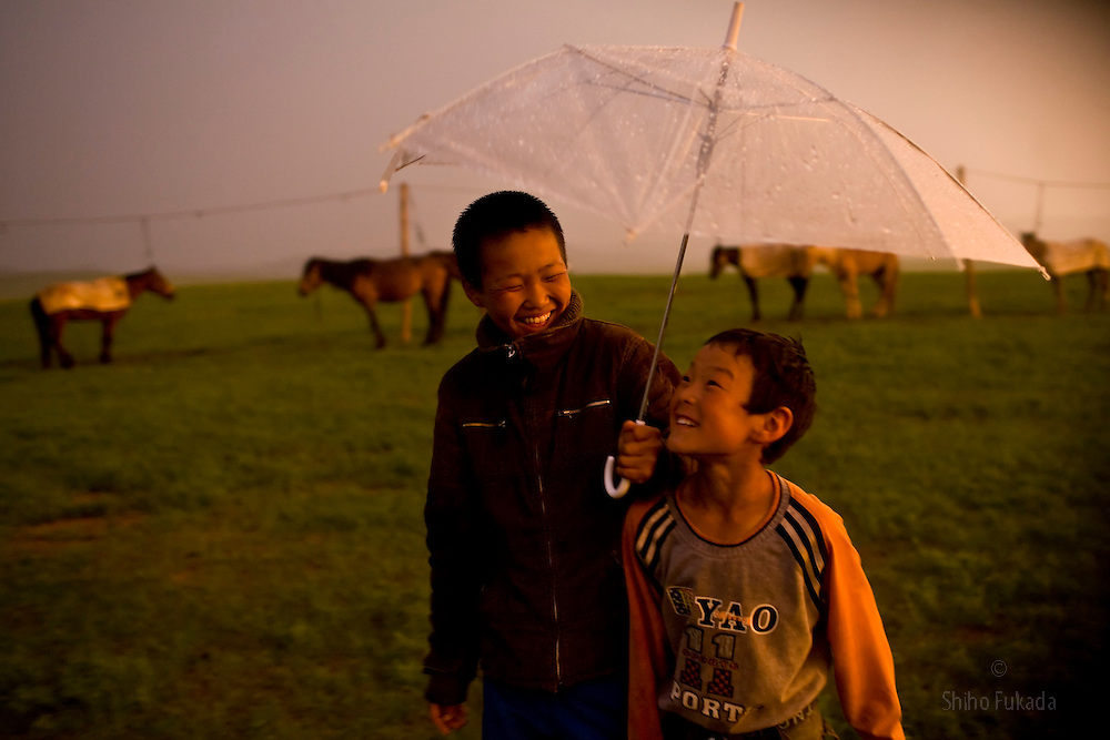 Mongolia - Edward Wong - Horse Race<br /> <br /> Boy jockeys takes shelter under an umbrella in the rain in Khui Doloon Khudag, Mongolia, July 8, 2008. Participants of this weekend's horse race during Naadam festival gather the area to practce. Children from 5 to 13 are chosen as jockeys. Photo by Shiho Fukada for The New York Times
