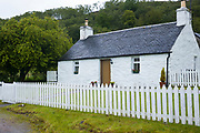 Quaint traditional whitewashed cottage with white paling fence and tiled roof in Appin, Argyll and Bute, Scotland