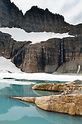 "Hike to Grinnell Glacier and powder blue Upper Grinnell Lake under the steep Lewis Range in Glacier National Park, Montana, USA. The spectacular 11 mile round trip walk (with 1700 feet gain) is shortened to 7.6 miles if you take two boat rides. Glaciers carved spectacular U-shaped valleys and pyramidal peaks as recently as the Last Glacial Maximum (the last ""Ice Age"" 25,000 to 13,000 years ago). Of the 150 glaciers existing in the mid 1800s, only 25 active glaciers remain in the park as of 2010, and all may disappear as soon as 2020, say climate scientists. Since 1932, Canada and USA have shared Waterton-Glacier International Peace Park, which UNESCO declared a World Heritage Site (1995) containing two Biosphere Reserves (1976). Rocks in the park are primarily sedimentary layers deposited in shallow seas over 1.6 billion to 800 million years ago. During the tectonic formation of the Rocky Mountains 170 million years ago, the Lewis Overthrust displaced these old rocks over newer Cretaceous age rocks."