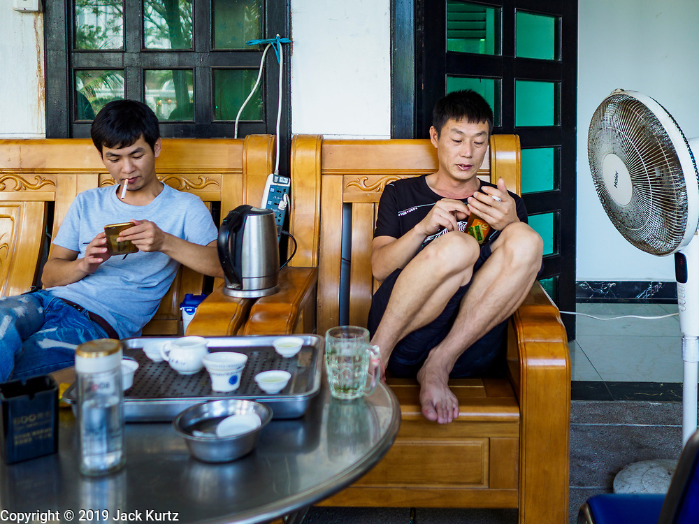 """14 FEBRUARY 2019 - SIHANOUKVILLE, CAMBODIA:  Men who work for Chinese enterprises in Sihanoukville in front of their apartment building. There are thousands of Chinese workers in Sihanoukville who work to support the casino and hotel industry in the town. There are about 80 Chinese casinos and resort hotels open in Sihanoukville and dozens more under construction. The casinos are changing the city, once a sleepy port on Southeast Asia's """"backpacker trail"""" into a booming city. The change is coming with a cost though. Many Cambodian residents of Sihanoukville  have lost their homes to make way for the casinos and the jobs are going to Chinese workers, brought in to build casinos and work in the casinos.      PHOTO BY JACK KURTZ"""