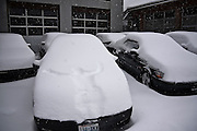 A man's imprint in the hood of a parked car covered in deep snow in Seattle, Washington.