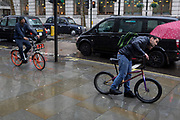 Two pavement cyclists pedal during heavy rainfall on an autumn afternoon on Charing Cross Road, on 24th October 2019, in Westminster, London, England.