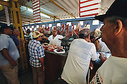 Buyers wait for their meat purchases in the Agromercado open agricultural market. A sign of the government's willingness to experiment with modest levels of free enterprise in the 1990s, the markets may not exist for much longer. In 2004 and 2005, Castro reined back the number of farmers allowed to work for themselves, stopped issuing many types of licenses for self-employment, and eliminated all traffic in U.S. dollars. Hungry Planet: What the World Eats (p. 103).