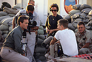 Scott Pelly interviews a soldier in Dharahan, Saudi Arabia in November 1990..Photograph by Dennis Brack
