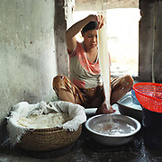 A pregnant woman making 'Bun' rice noodles outside her home in Mach Trang village, Hanoi, Vietnam. With Vietnam's growing population making less land available for farmers to work, families unable to sustain themselves are turning to the creation of various products in rural areas.  These 'craft' villages specialise in a single product or activity, anything from palm leaf hats to incense sticks, or from noodle making to snake-catching. Some of these 'craft' villages date back hundreds of years, whilst others are a more recent response to enable rural farmers to earn much needed extra income.