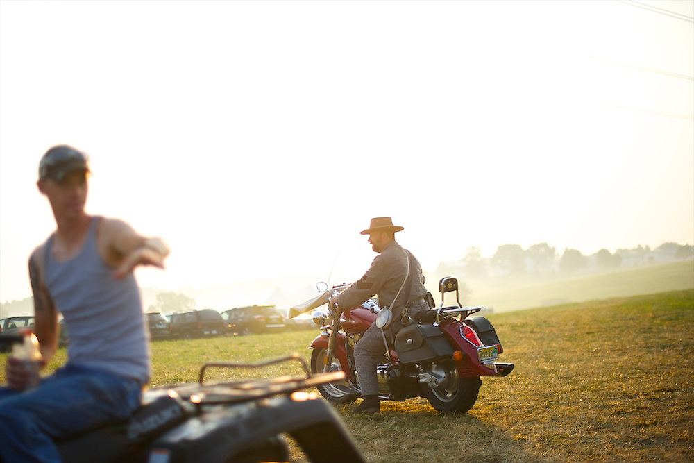 With his rifle resting on the handlebars, a Confederate soldier arrives on his motorcycle in the early hours of morning for the second day of the 149th Gettysburg Reenactment in Gettysburg, Pennsylvania on July 7, 2012.