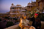"""Nobleman Nahar Singhji, also known as Rao Saheb, relaxes  with his wife Rani Saheb on a terrace of the Deogarh Mahal (Fort - Palace) a 340 year old architectural jewel. She being the chief decorator of the now heritage hotel, after the family had no way of maintaining it's upkeep. His family belonged to the Umroa's of Udaipur. """"Lords"""" of the State of Mewar, paying allegiance to the Maharana of Udaipur. Eight generations of his family have lived in the Deogarh fort after which in 1996 it was converted into a hotel, Udaipur, Rajasthan, India"""