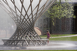Stock photo of a little girl enjoying the Mist Tree fountain on a hot afternoon