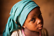 "Latifa, 8, poses for a photograph at her home in Saran Maradi, Niger.<br /> Her grandmother Delou Ibrahim, 70, has four children and suffered the loss of nine. She has about 40 grandchildren, 16 of which live with her. <br /> ""I've seen several crises. The famine in 1984 was the hardest. Rains were very weak. The stems of millet came out but the spikes gave no grain - nothing,"" she recalls. ""Two years ago at least there were people who harvested millet, but this year the crops have been worse because of the drought and the leaf miners."" Delou's last crop was 30kg, which only provided food for about two days.<br /> Delou and her family receive cash from CARE. ""I get to buy cereal to feed my family, particularly my grandchildren."" They have two daily meals, porridge in the morning and sorghum paste in the evening."