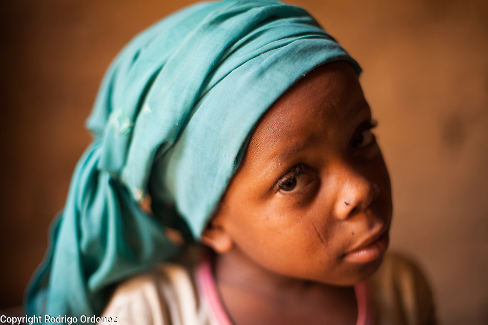 """Latifa, 8, poses for a photograph at her home in Saran Maradi, Niger.<br /> Her grandmother Delou Ibrahim, 70, has four children and suffered the loss of nine. She has about 40 grandchildren, 16 of which live with her. <br /> """"I've seen several crises. The famine in 1984 was the hardest. Rains were very weak. The stems of millet came out but the spikes gave no grain - nothing,"""" she recalls. """"Two years ago at least there were people who harvested millet, but this year the crops have been worse because of the drought and the leaf miners."""" Delou's last crop was 30kg, which only provided food for about two days.<br /> Delou and her family receive cash from CARE. """"I get to buy cereal to feed my family, particularly my grandchildren."""" They have two daily meals, porridge in the morning and sorghum paste in the evening."""