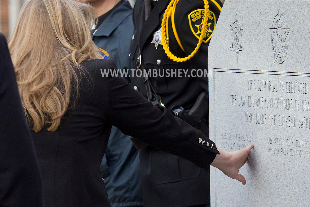 Goshen, New York - A woman touches a name on a monument during the Orange County Law Enforcement Officer Memorial Service on May 2, 2014. The memorial service honors the memory of the 27 members of the Orange County law enforcement community that died in the line of duty. The service also pays tribute the families and loved ones left behind for their courage, dignity and perseverance.