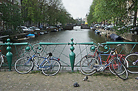 Bikes lean on an ornate old green fence on a bridge over a canal in Amsterdam.