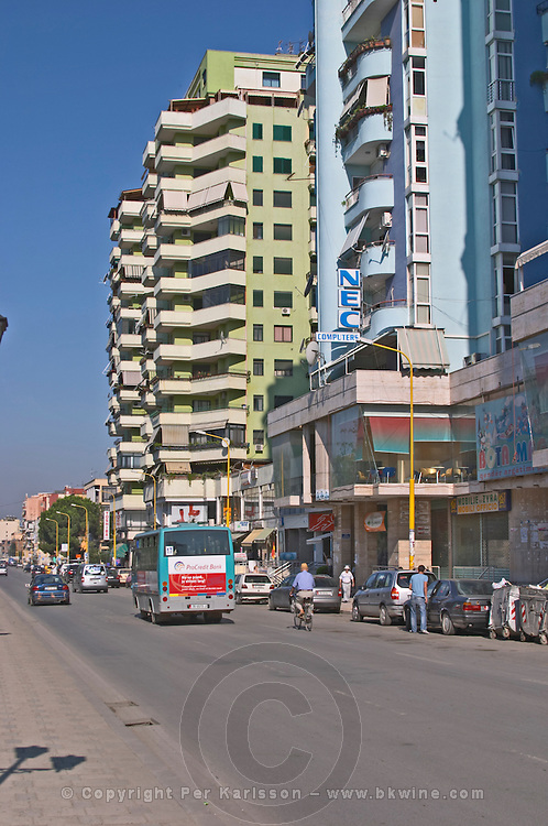 Street scene in with tall modern colourful apartment buildings a bus, people walking on the street. Tirana capital. Albania, Balkan, Europe.