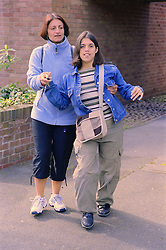 Teenage girl with physical disability walking along street with assistance of her mother,