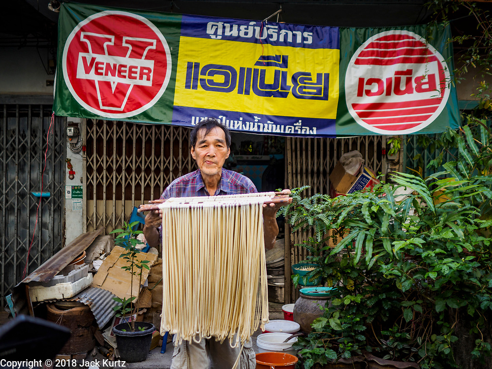 """29 DECEMBER 2018 - BANGKOK, THAILAND: A man carries longevity noodles out of the shophouse to drying racks in front of his home. The family has been making traditional """"mee sua"""" noodles, also called """"longevity noodles"""" for three generations in their home in central Bangkok. They use a recipe brought to Thailand from China. Longevity noodles are thought to contribute to a long and healthy life and  are served on special occasions, especially Chinese New Year, which is February 4, 2019. These noodles were being made for Chinese New Year.        PHOTO BY JACK KURTZ"""