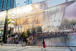 Woman walking past large billboard showing proposed new Opera House under construction in Downtown Dubai United Arab Emirates