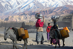 Women carry washed dishes and pots back to their home which is about two Kms from the water source. This daily journey takes up considerable energy and time. Bamyan town, Bamyan province, Afghanistan