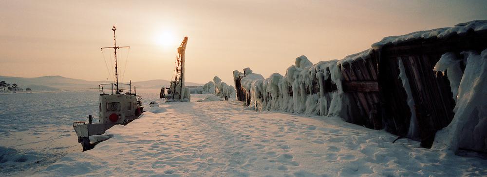 Fishing boat frozen in harbour at Olkohn Island, Lake Biakal, Siberia, Russia