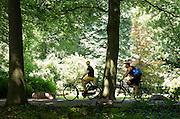 Bij Rhijnauwen passeert een sportieve fietser een man op een stadsfiets. Veel mensen genieten van het mooie weer, door te wandelen, te fietsen of een pannenkoek te eten bij het pannenkoekenrestaurant.<br /> <br /> A fast cyclist is passing a man on a city bike near Rhijnauwen. People are enjoying the nice weather by walking, cycling or eating pancakes.