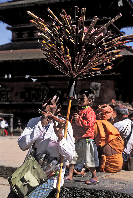 Flute seller playing one of his flutes, a parasol of many flutes above his head.  Durban Square in Bhaktapur during Dasain holiday, 2001..