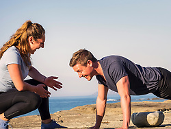 Woman with man doing push-ups on the beach of Azkorri
