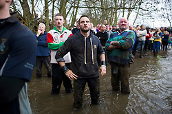 © London News Pictures. 05/03/2014. Ashbourne, UK. Competitors watch over from stood in a river. DAY TWO as  the Up'Ards and the Down'Ards, fight for the ball during the second day of the Royal Shrovetide Football match in Ashbourne, Derbyshire. For two days, over Shrove Tuesday and Ash Wednesday, hundreds of participants battle it out in a 'no rules' game dating back to the 17th Century where the aim is to get a ball into one of two goals that are positioned three miles apart at either end of Ashboune. Photo credit: Ben Cawthra/LNP