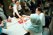 Nederland, Tilburg, 10-10-2003..allochtone leerling zonder hoofddoek van een middelbare school trakteert snoep aan allochtoon meisje met hoofddoek tijdens pauze in de hal, aula, kantine. Onderwijs, intergratie, multicultureel..Foto: Flip Franssen/Hollandse Hoogte