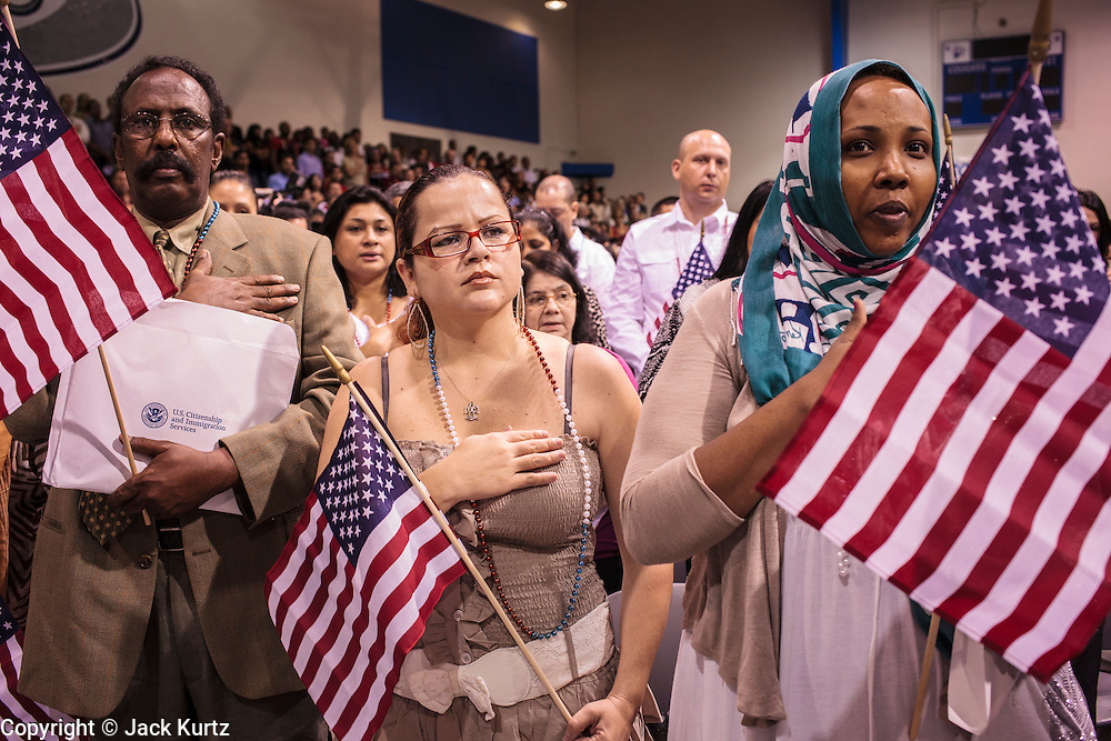 04 JULY 2012 - PHOENIX, AZ: OMAR YUSUF, left, originally from Somalia, MARGARITA BASRTO, originally from Mexico, and SUMAYO AHMED, originally from Somalia, take the oath as US citizens Wednesay. About 250 people, from 62 countries, were naturalized as US citizens during the 24th Annual Fiesta of Independence naturization ceremony at South Mountain Community College in Phoenix Wednesday. The ceremony was presided over by the Honorable Roslyn O. Silver, Chief United States District Court Judge.    PHOTO BY JACK KURTZ