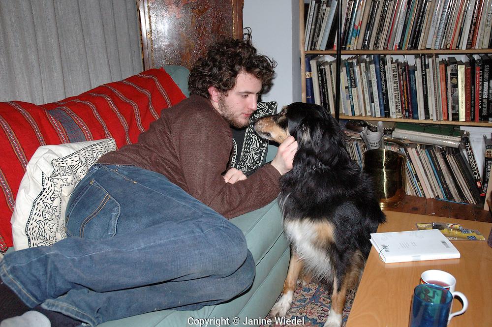 Young man at home with pet border collie.